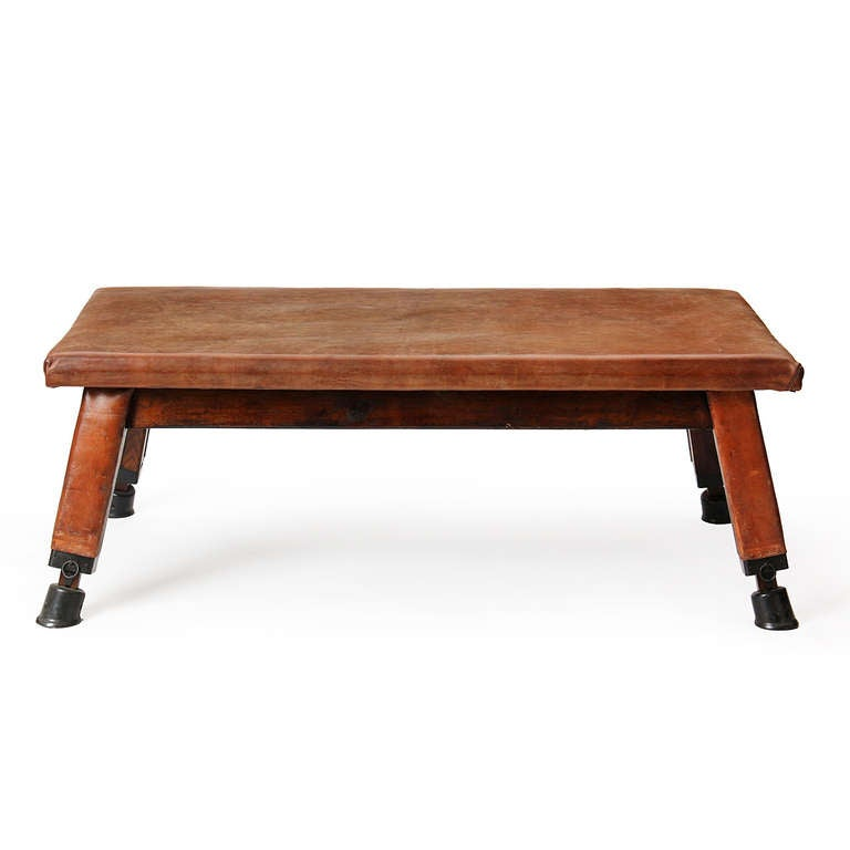 A leather covered gymnastics bench on splayed, leather-clad, ebonized pine legs with patinated cast iron feet.