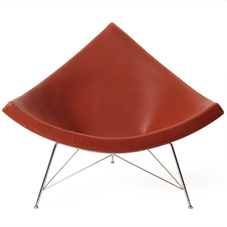 An excellent example of Nelson's iconic coconut lounge chair, with its original brick-red leather upholstery on splayed, chromed steel legs.