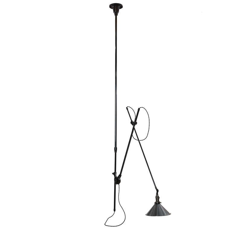 A ceiling-mounted and fully articulated industrial lamp having a rich dark patinated finish, steel conical shade and a sculptural cast iron ceiling plate.