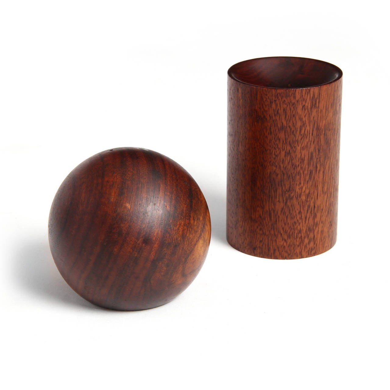 A spare and geometric nesting salt and pepper shakers having the form of a circle and a cylinder perfectly executed in richly figured solid teak.