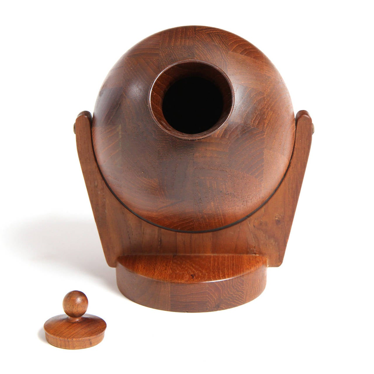 A wall-mounted lidded tobacco vessel having a rounded tilting form on mounted arms crafted of turned and carved richly figured teak.