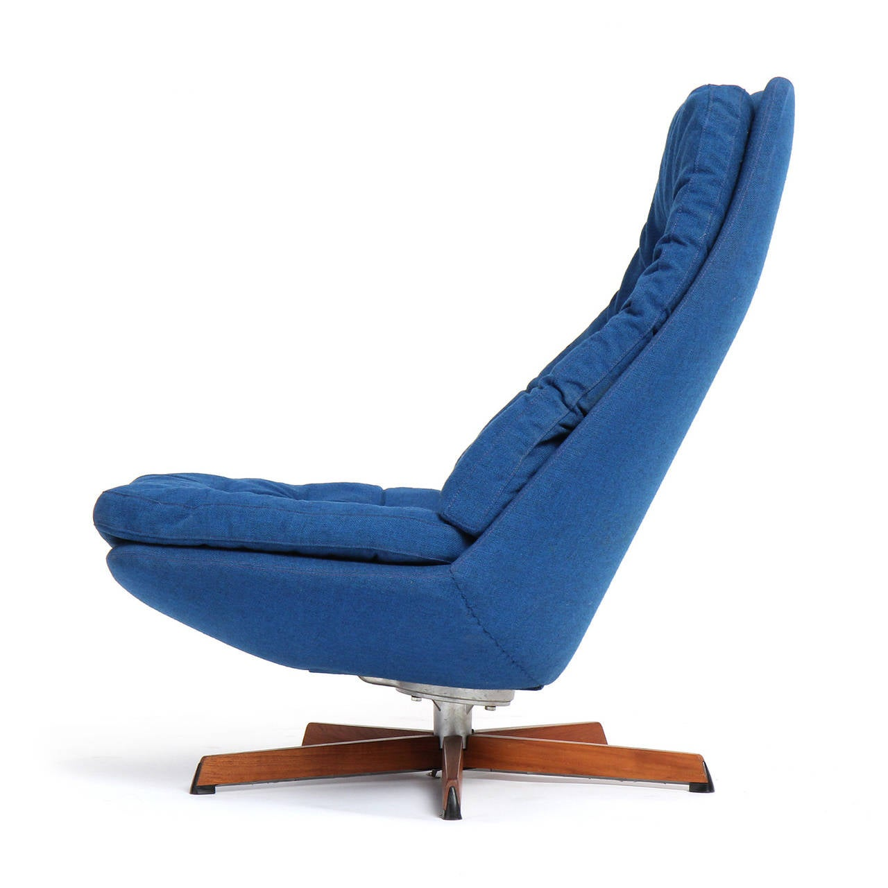 A sculptural low slung swiveling button tufted lounge chair having rich deep blue wool upholstery and floating atop a five-armed aluminum and teak base.