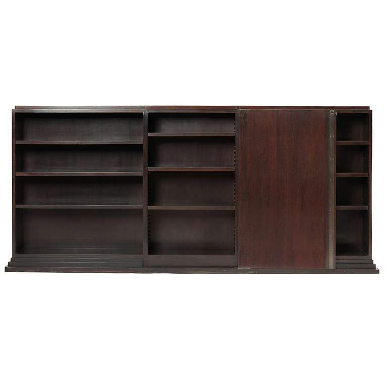 An elegant and beautifully proportioned Art Deco rosewood bookcase or cabinet having three shelved sections with a sliding single door, the entire structure rising from a stepped base.