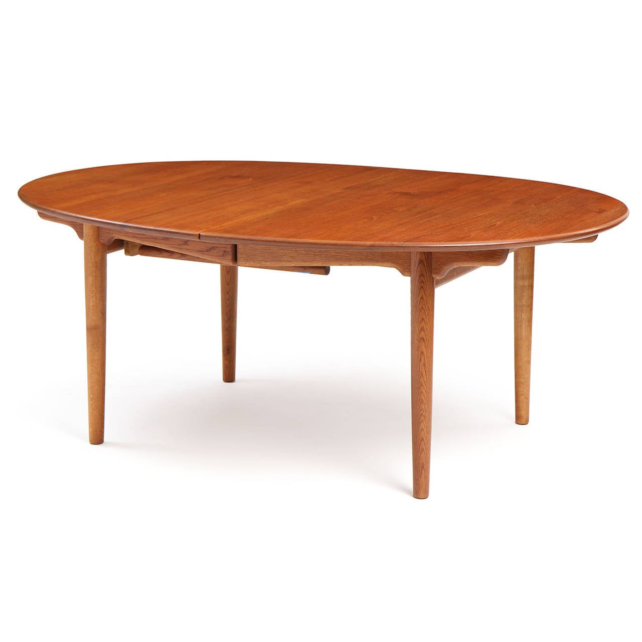 An oval extension dining table with tapered dowel legs and cloud lift stretchers. Three 25
