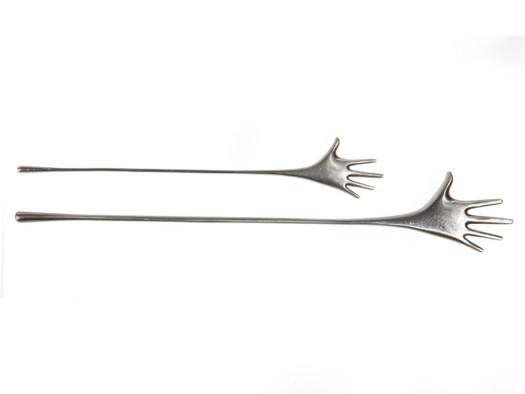 A nickel plated brass drink stirrer in the form of a hand.