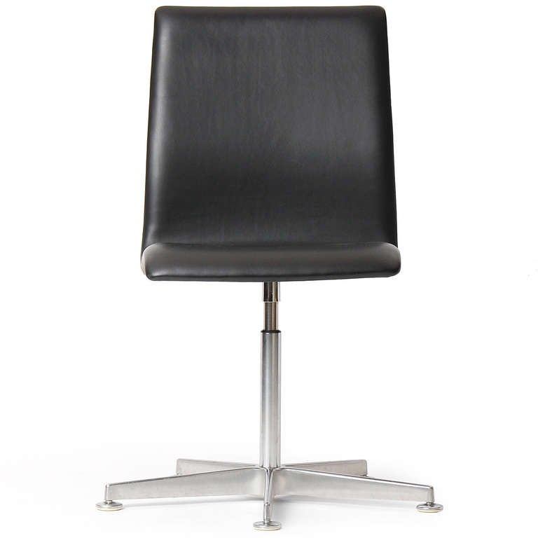 A swiveling 'Oxford' chair designed by Arne Jacobsen featuring a low black leather back on a cast aluminum five point base. Made in Denmark by Fritz Hansen.