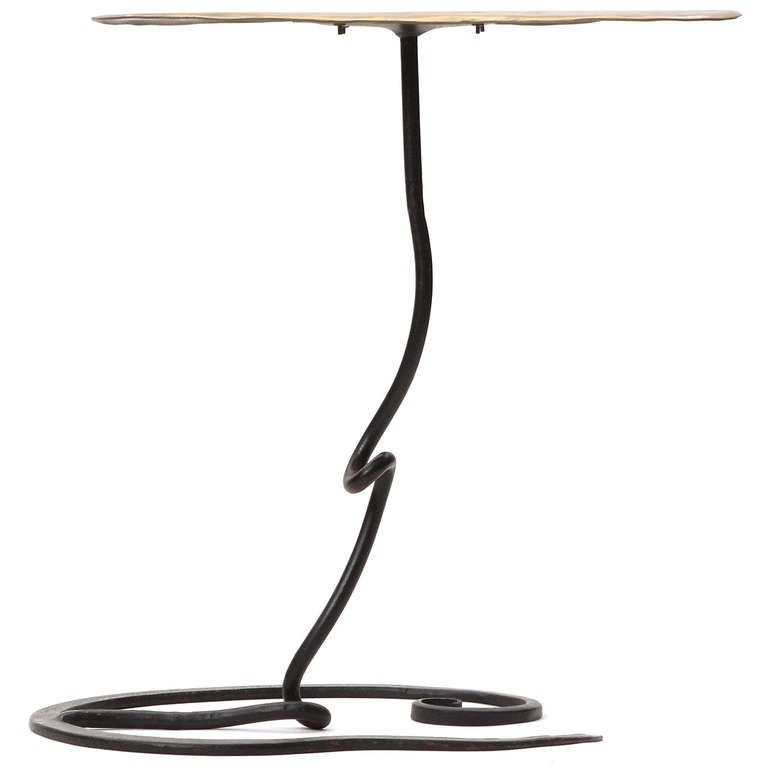 A handcrafted, sculptural side table having a patinated biomorphic bronze top floating atop an undulating wrought iron base.
