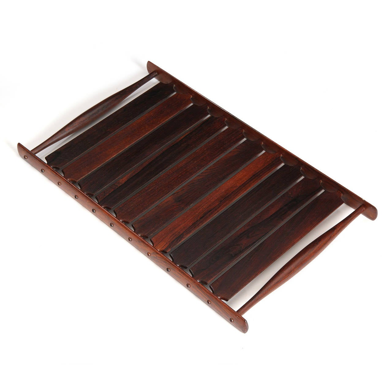 A beautifully constructed Brazilian rosewood serving tray, comprised of ten radius backed slats with fingered tenons mortised through the oval formed side rails, flanked by swollen dowel handles (from the