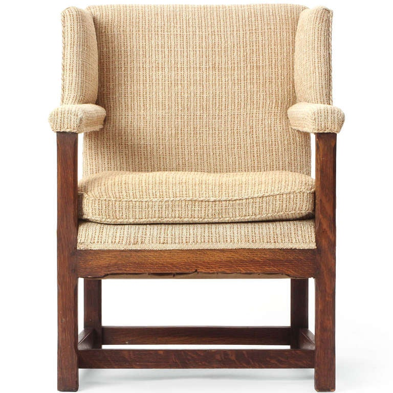 A well-proportioned wingback chair having a rectilinear base in quarter-sawn oak, fully upholstered arms, expressive shortened wings and a down-filled seat cushion.