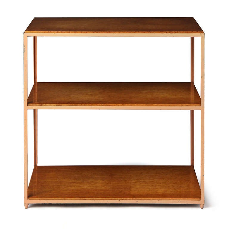 An architectural three-tiered end table with burl Finnish birch shelves supported by a steel frame.