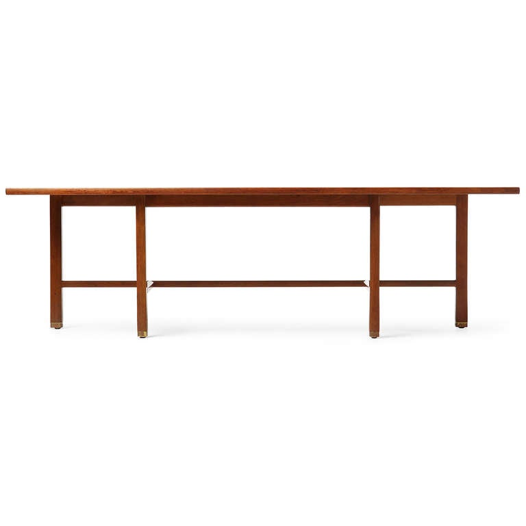 A low console or table with a spare mahogany frame that supports an asymmetrical top with brass capped feet.