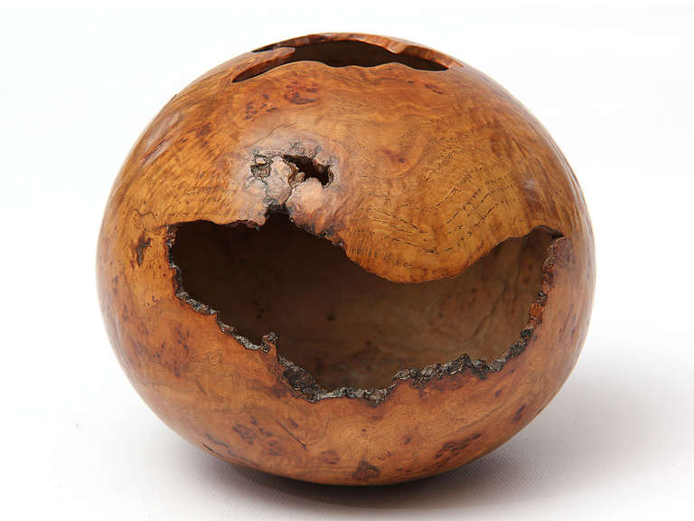An exceptional turned hollow form vessel with a near perfect spherical shape and large natural opening. Signed