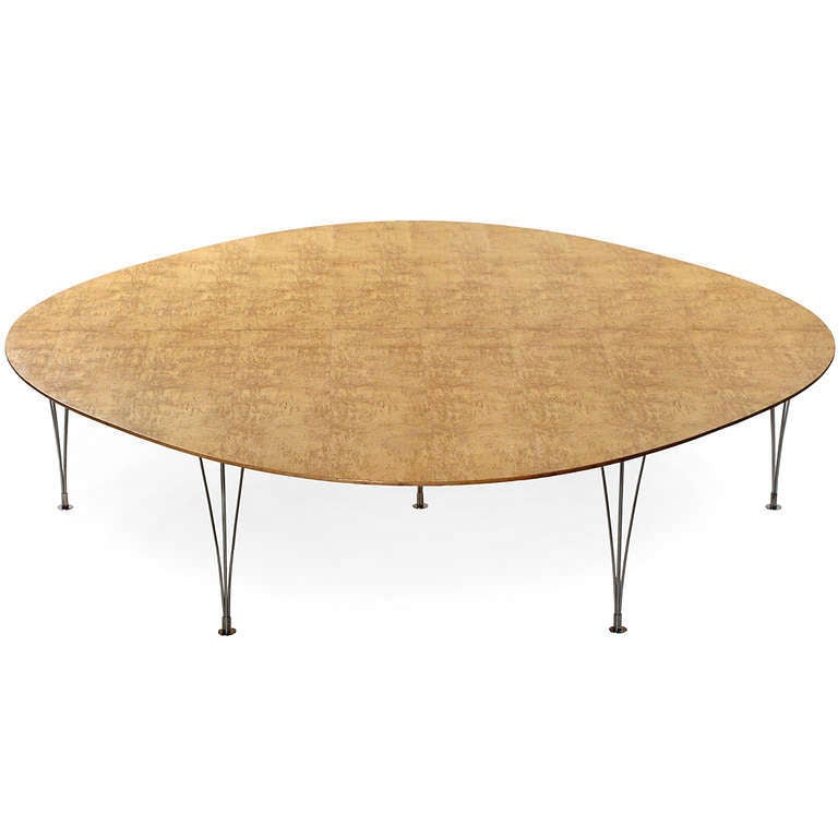 A rare 'Super Ellipse' conference or dining table designed by Piet Hein with a top in figured birch burl and tapering chromed steel legs.  Besides the unique shape of the top, the ingenious design detail on this table is that the legs bracket into