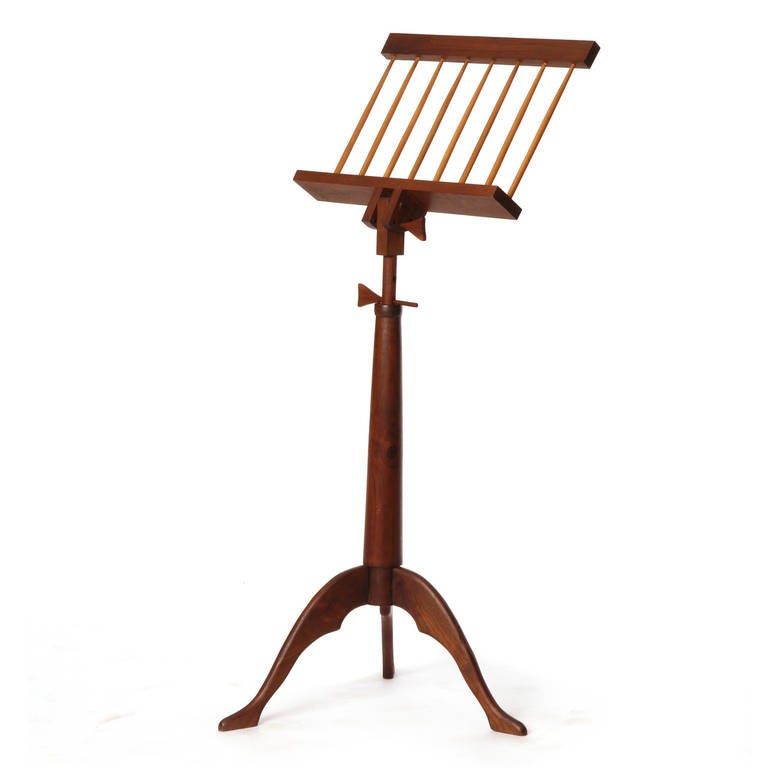 A great handcrafted walnut music stand with adjustable pitch and adjustable height via holes and dowels atop a tripod base.