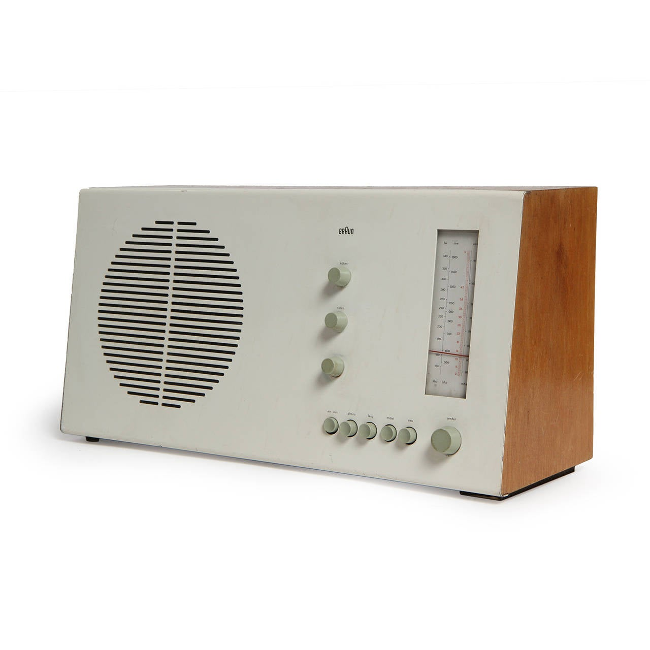 A spare modernist desk radio devoid of extraneous detailing having a distinctive slanted powder-coated sheet steel front and honey-toned beech wood on the sides.