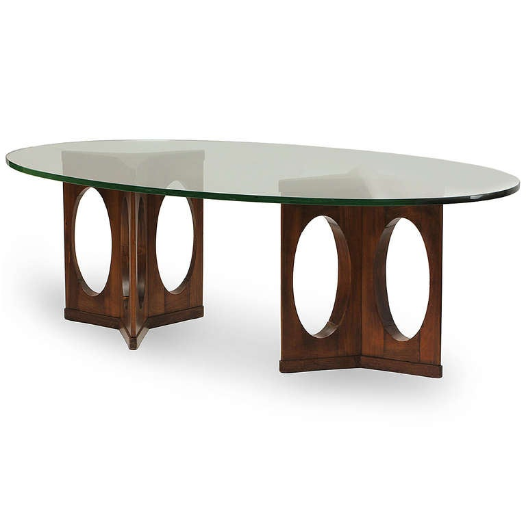 A custom-designed dining or conference table with two wood triangulated open bases supporting a long oval glass top.