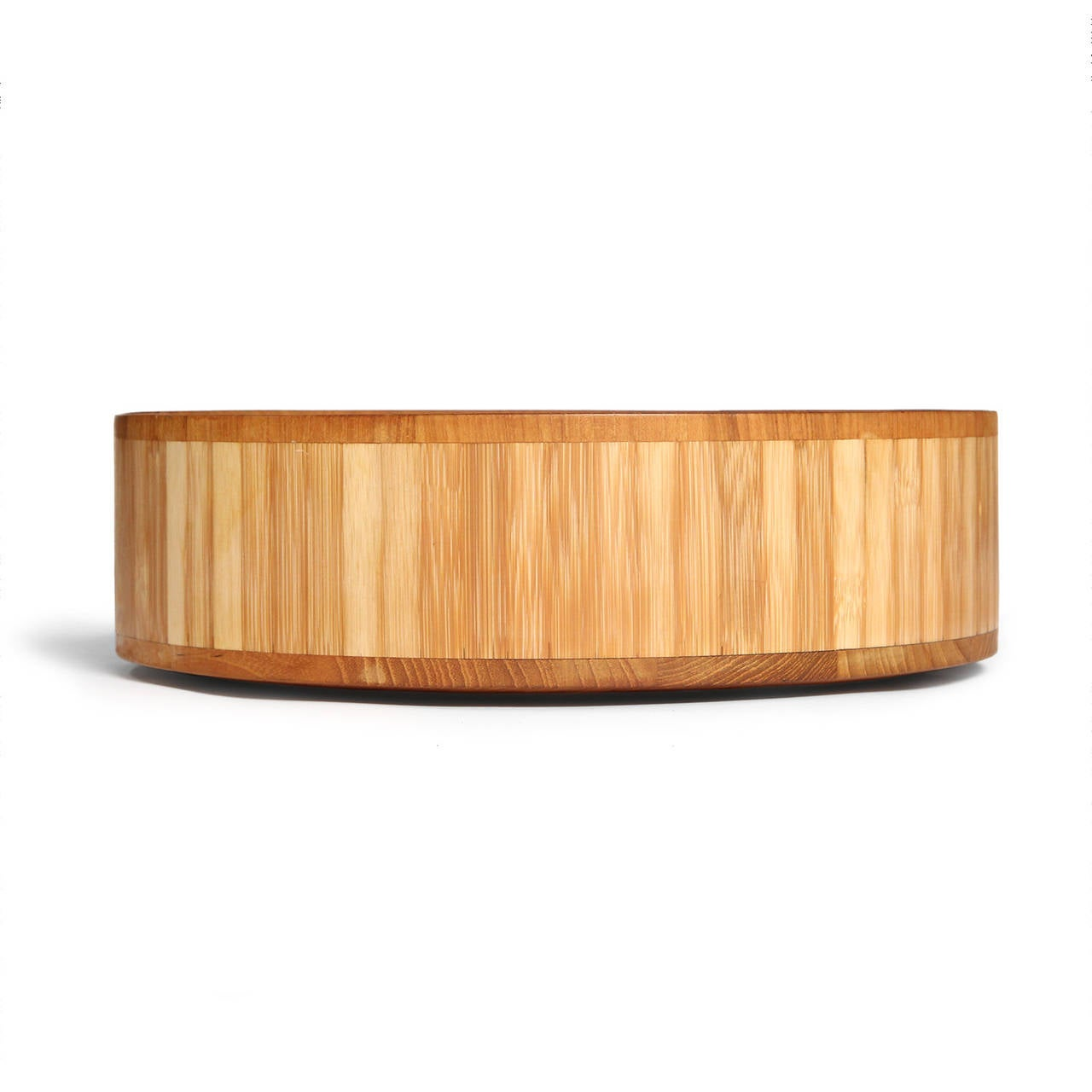 A beautifully crafted, well scaled and rare staved teak serving bowl encircled by vertical slats of pale bamboo.