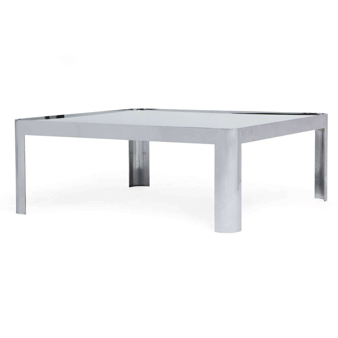 A substantial modernist low table having a one-piece heavy forged polished stainless steel base with rounded corners and legs supporting a floating mirrored glass top.