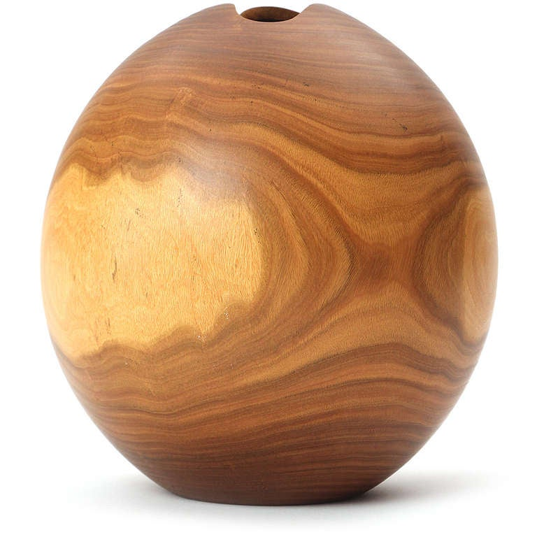 A beautifully grained and masterfully turned spherical vase turned from a single piece of Clao walnut and having an expressive free-formed opening.