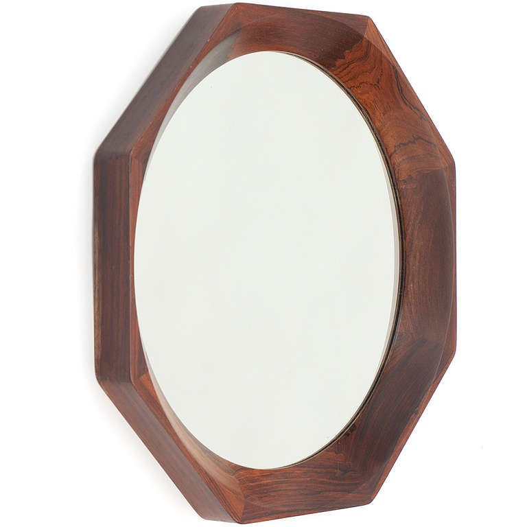 An octagonal geometric wall mirror, constructed of carved and shaped figured rosewood.
