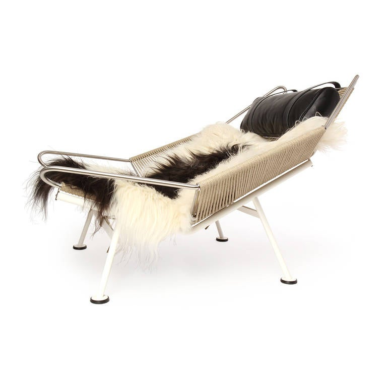 An iconic and dramatic lounge chair having a sculptural and engineered stainless steel frame with a seat and back made of plaited flag halyard. Comfort is added with a longhaired sheepskin throw and an adjustable leather headrest.