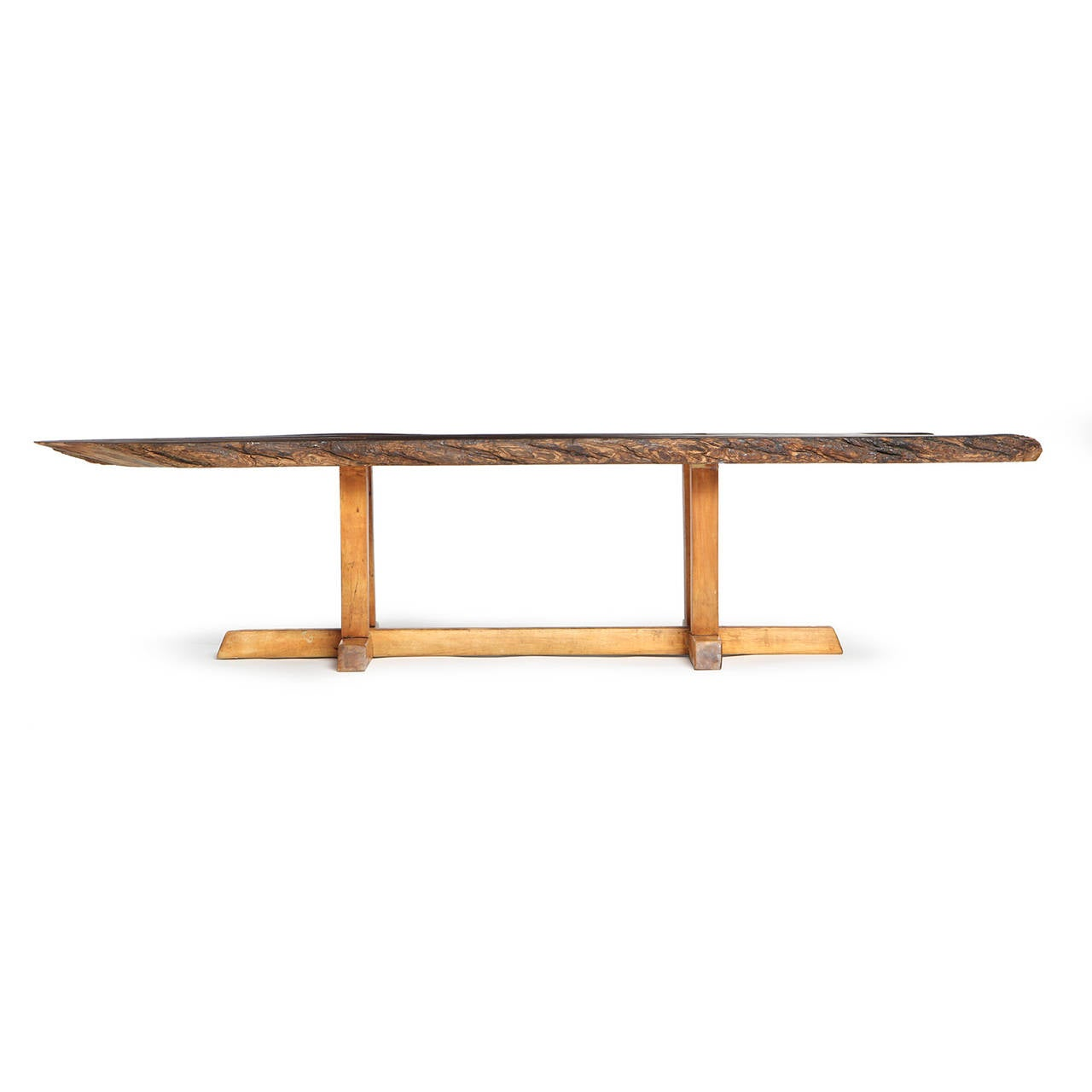 An expressive and finely crafted low table having a live edge walnut top floating on an architectural base.