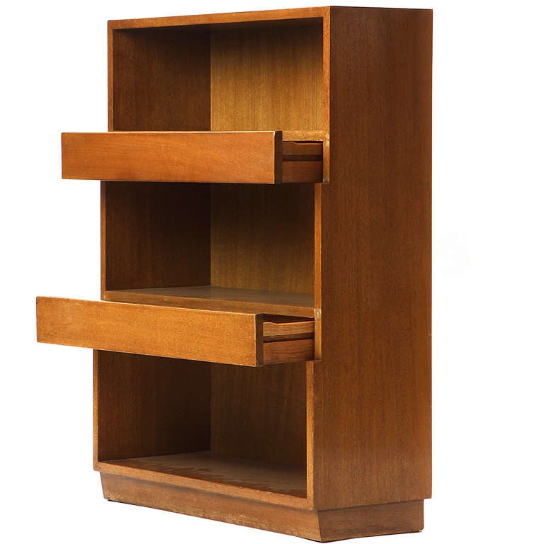 A mahogany bookcase with stepped front and two drawers between the shelves, on a recessed plinth base.
