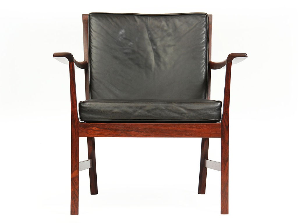 An elegant and generously proportioned arm chair having an architectural exposed frame with discretely curved arms.