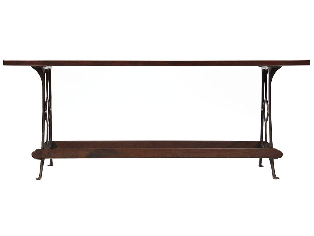 A high, narrow freestanding Industrial counter table with a solid mahogany top and footrails, on patinated, cast-iron legs, the total length is determined by the wood dimensions. Custom width/length available.
