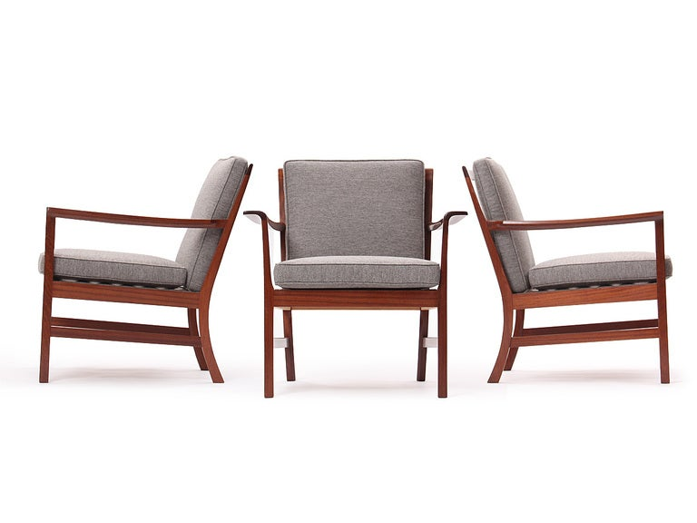 A generously proportioned Scandinavian Modern lounge chair designed by Ole Wanscher for A.J. Iversen. This chair features an architectural exposed Cuban mahogany frame with shaped and discretely curved arms. Seat and Back cushions upholstered in