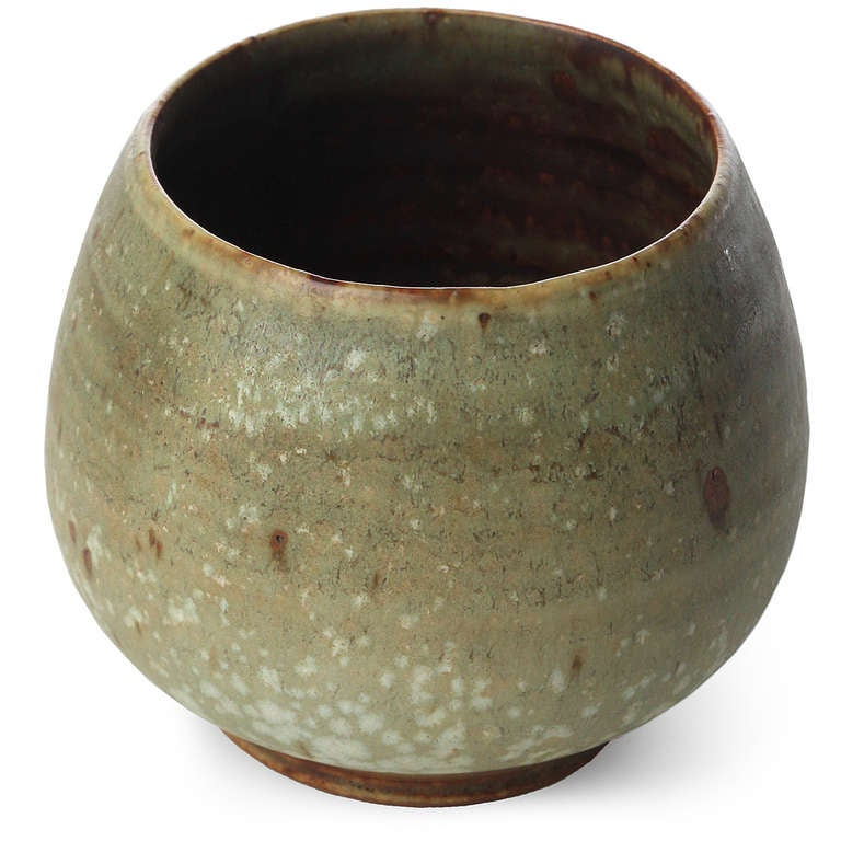 A diminutive hand-thrown studio-made footed stoneware vessel having a rustic and complex crystalline glaze.