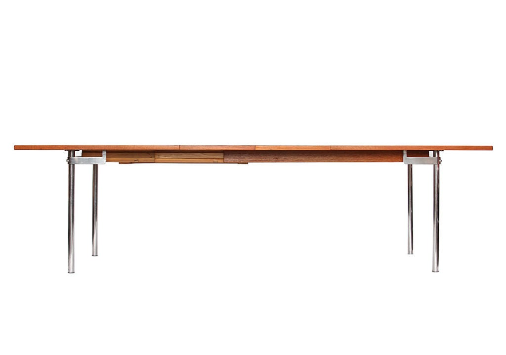 An extension dining table with a rectangular teak top on satin-chromed steel pipe legs. Measures: Leaves (16