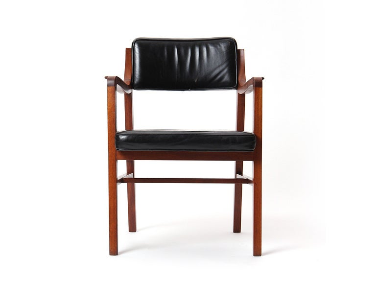 A sculptural and finely detailed armchair in teak having a floating seat and back cushions, retaining the original black leather upholstery.