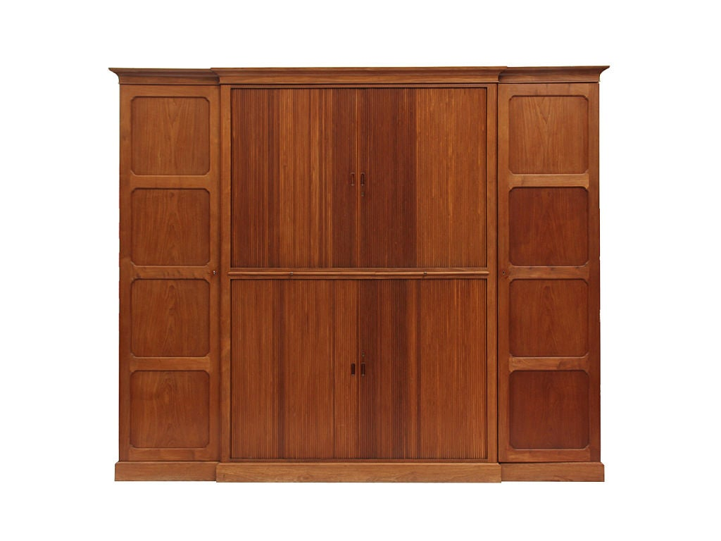 A custom, solid mahogany breakfront cabinet with a crown moulding, on a plinth base. The central section with two pairs of reeded tambour doors, opening to numerous oak shelves, flanked by one enclosed compartment with adjustable shelves, and one