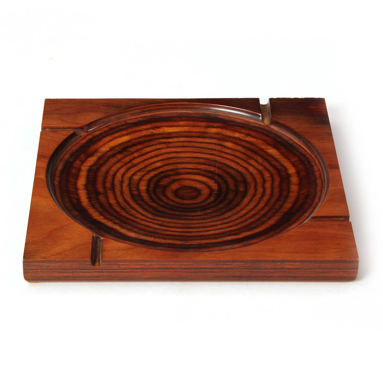 A striking geometric ashtray fashioned from a square of stratified and stained plywood having a delicately scooped bowl and routed channels for cigarettes.