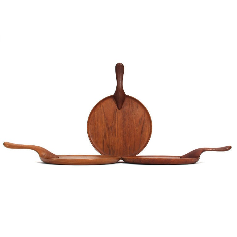 A finely crafted solid teak serving tray with a carved sculptural handle.