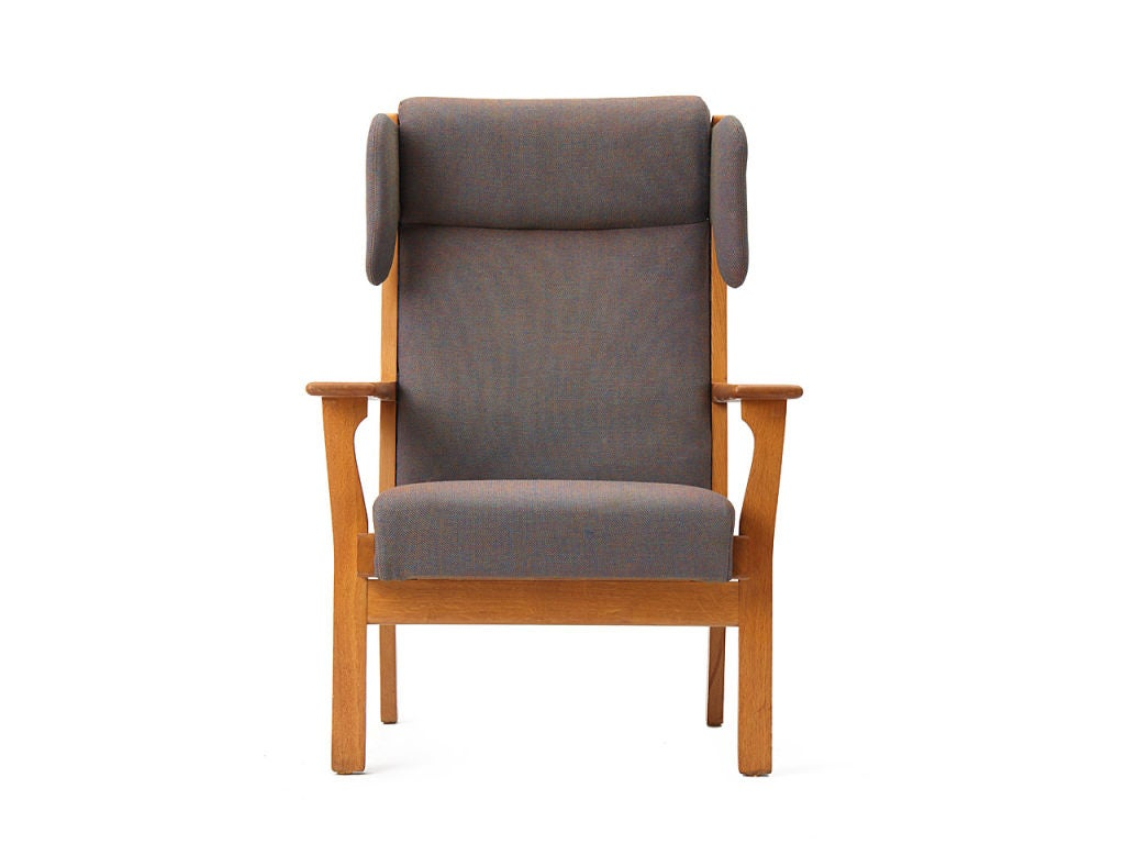 A wingback lounge armchair with a teak frame, retaining the original grey wool upholstery.
