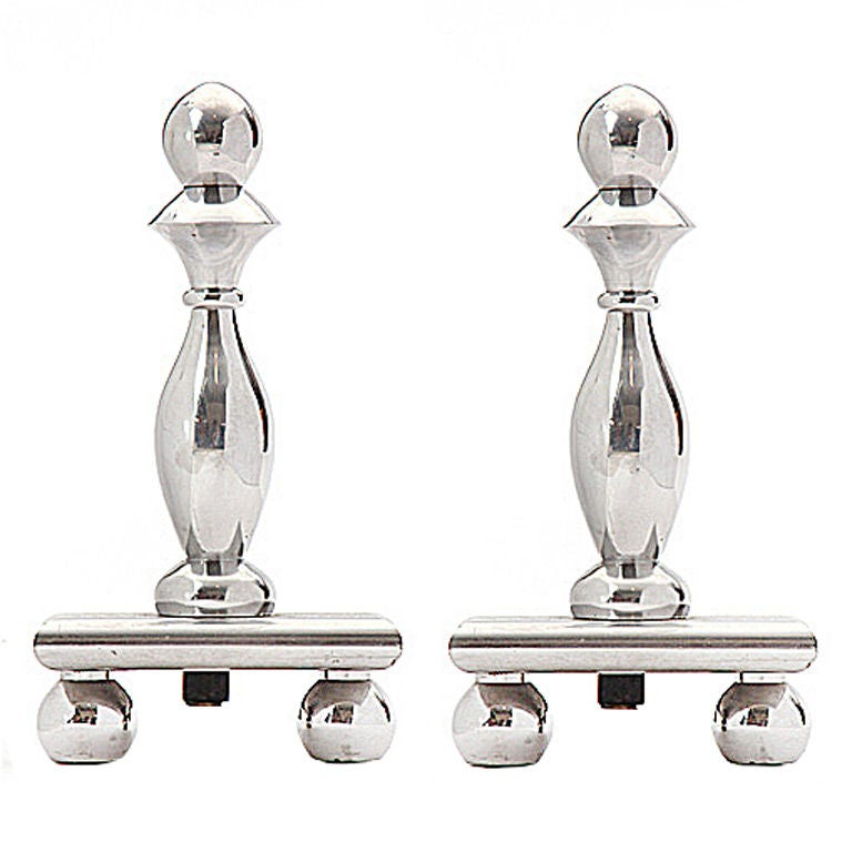A pair of chromed steel and wrought iron andirons, with