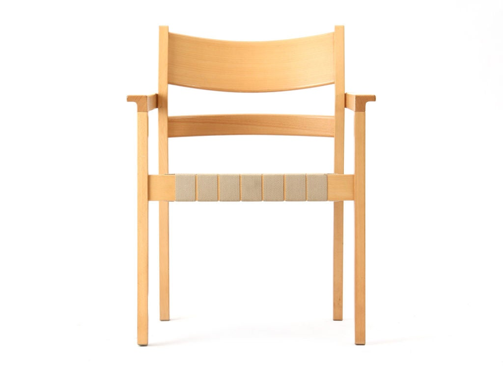 A set of four stacking armchairs with cream webbed seats in beechwood.