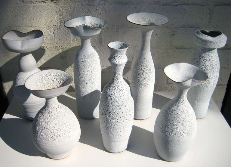 A group of seven hand thrown terra cotta vessels with a white