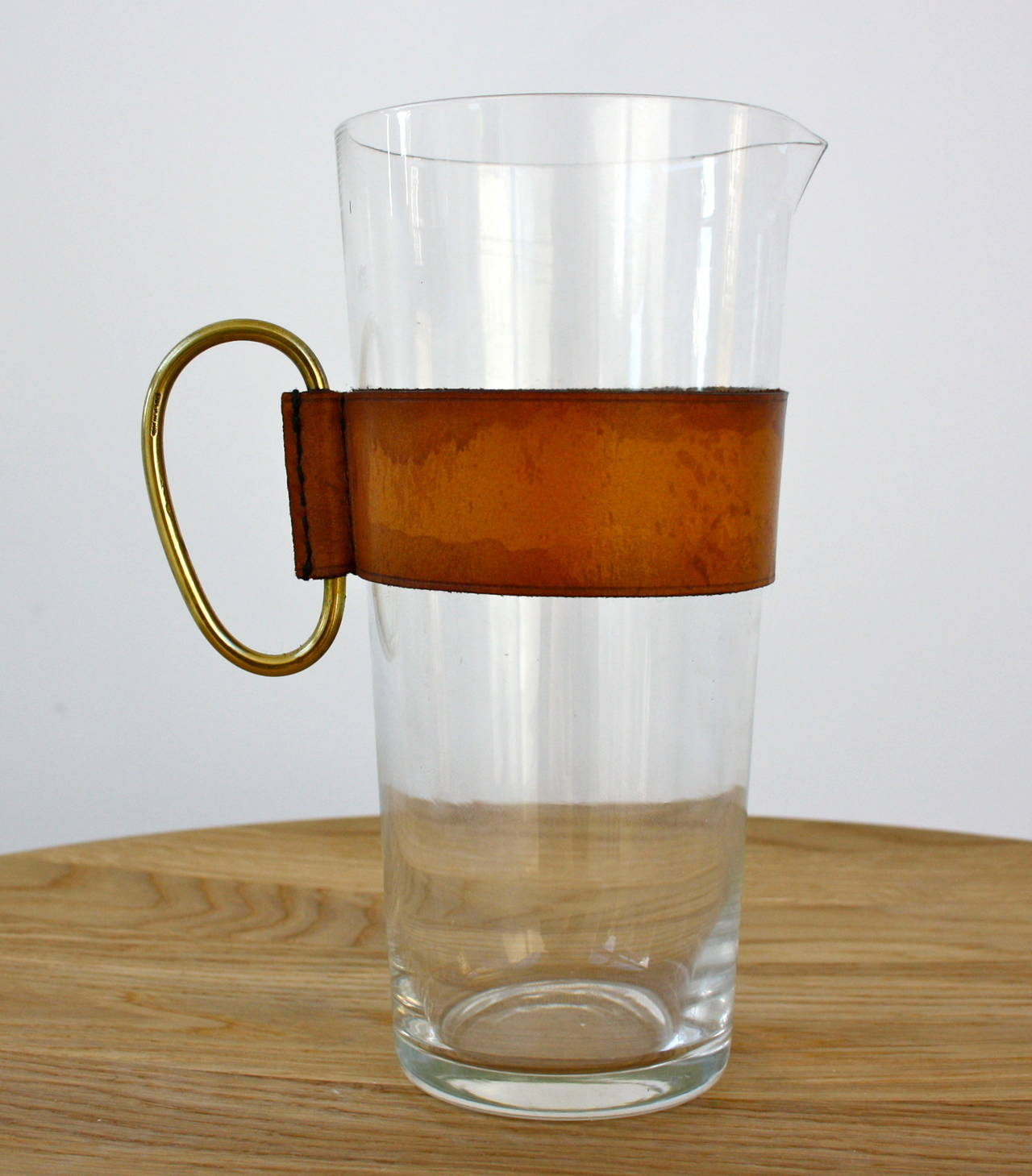 Glass, leather and brass pitcher by Carl Auböck. Made in his workshop in central Vienna.