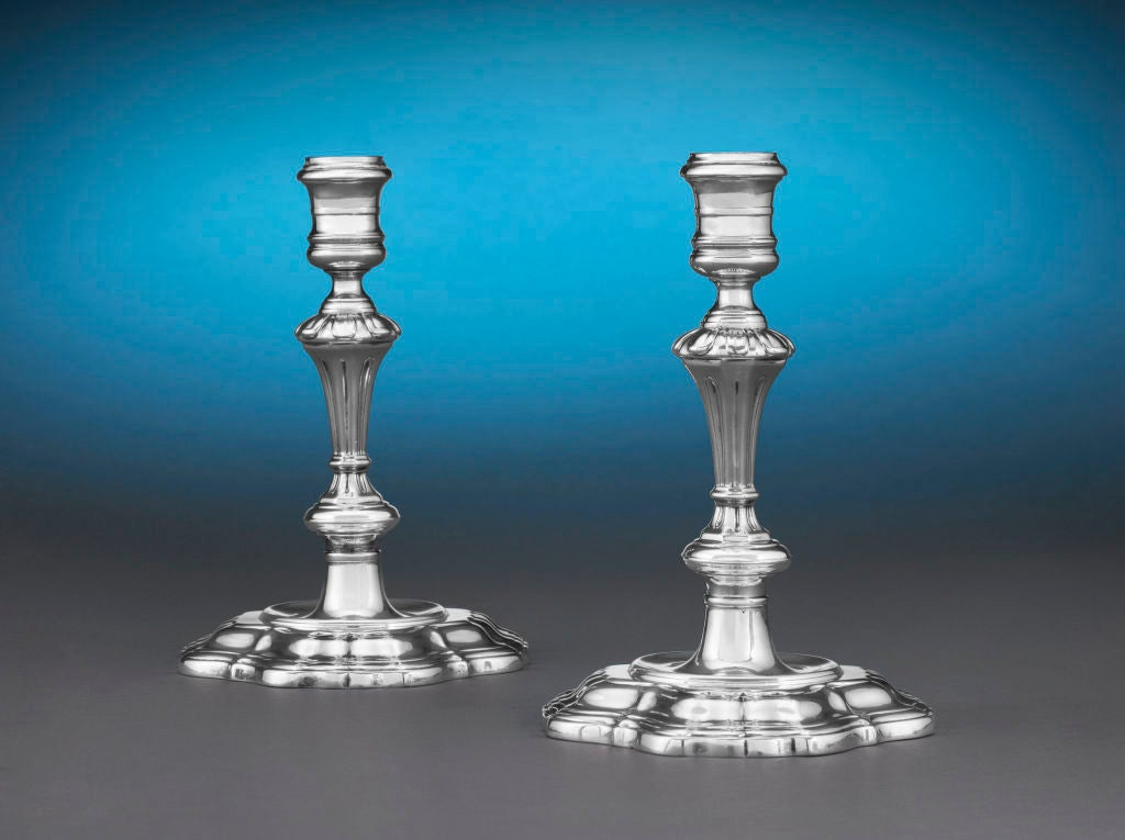This rare and elegant pair of George II period silver candlesticks was crafted by renowned master silversmith Paul de Lamerie. Exhibiting the understated sophistication of the Georgian style, these lights are testament to de Lamerie's unmatched eye