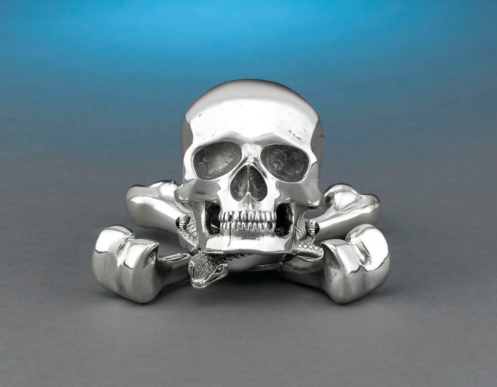 This remarkable Jolly Roger desk clock is one of only 10 such timepieces created by the celebrated Swiss watchmaking firm of Corum. The entire case is crafted of solid sterling silver in the piratic skull and cross-bones, and houses a quartz