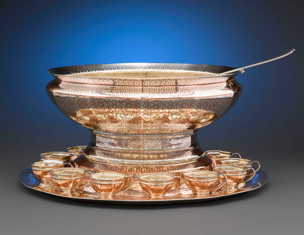 An extremely rare and desirable antique Tiffany Co, sterling silver and copper inlay punch service. Consisting of a generous punch bowl, weighing an incredible 335 ounces, a plateau, twelve cups and a matching ladle, this magnificent service