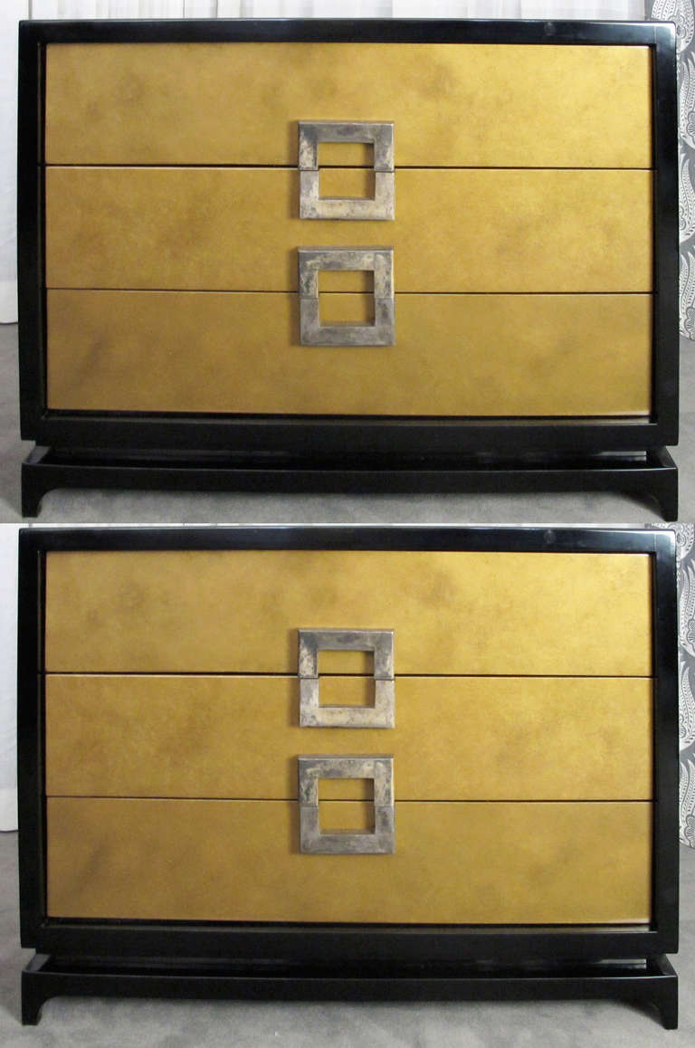 This is a very handsome and decorative pair of chests or dressers attributed to Archibald Taylor.  Decorative gold drawers fronts are framed by a black-lacquered case.  Antiqued nickel square pulls provide function and decoration.  NIcely refinished.