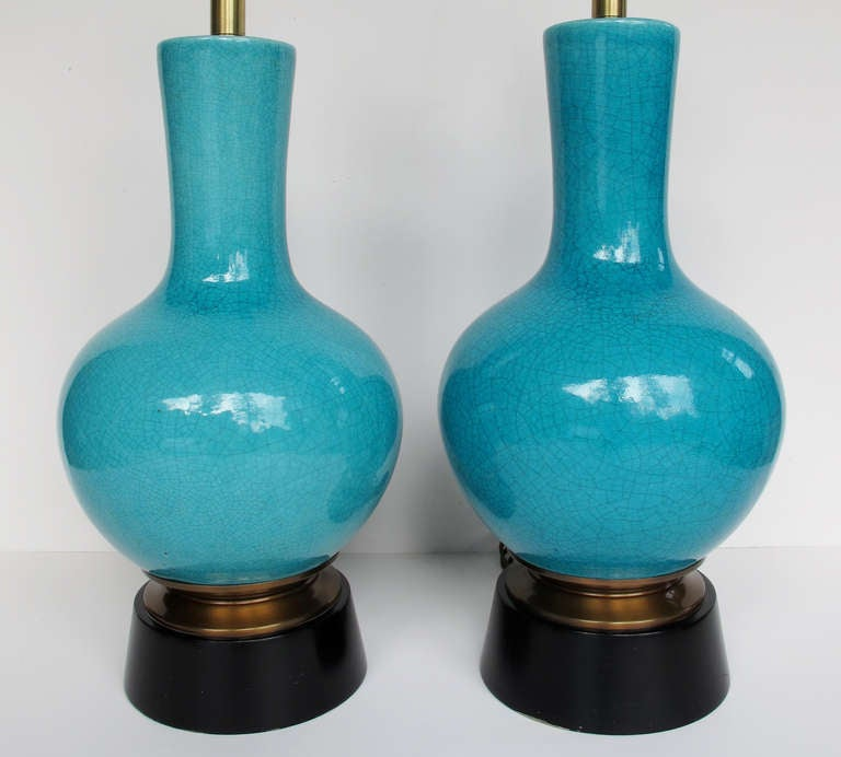 This is substantial pair of lamps in a gorgeous turquoise crackle glaze designed by Paul Laszlo and made by Wilshire House.  The ceramic vasiform base is mounted on a brass and ebonized wood plinth.  Lamps measure 19 inches to the top of the pottery