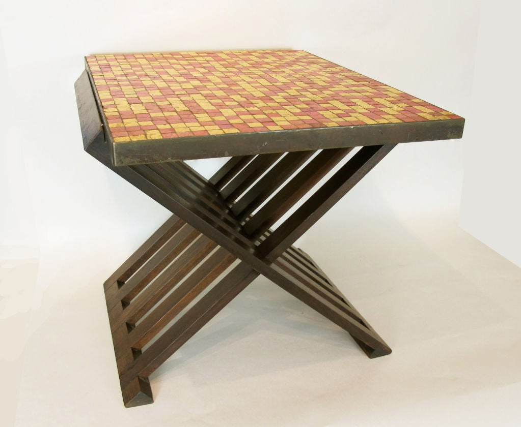 A hard-to-find Wormley-designed table for Dunbar with Murano glass tile top captured in brass frame. Brass frame is unpolished and has a dark patina. Mahogany x-shaped base appears to be in its original, unrefinished state.