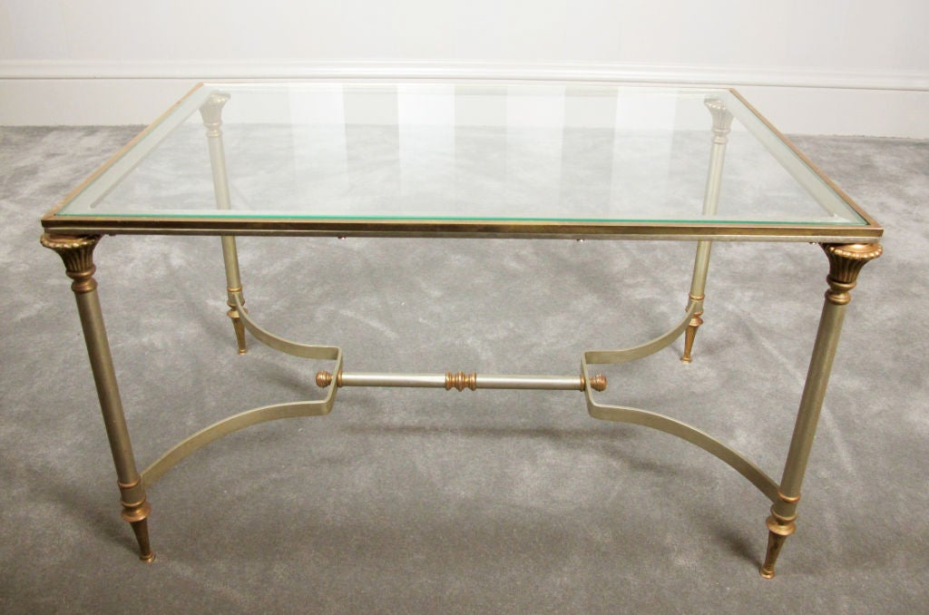A very stylish cocktail or coffee table in the style of Maison Jansen, but most likely of American origin.  Well made and heavy, table is in excellent vintage condition with what appears to be the original glass top.