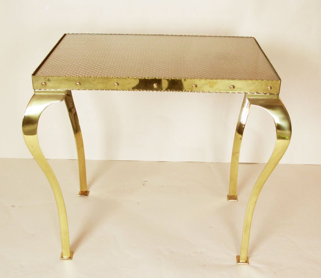 A pair of highly unusual and decorative brass tables which look to be of Italian origin, although previous owner stated they were Swedish. The brass apron captures a sheet of glass and also a sheet of brass open-weave mesh that allows the color of a