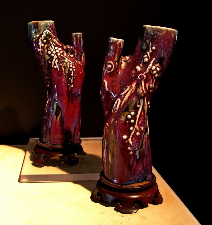 A pair of vases molded as naturalistic plum tree trunks, with applied decorations of flowering plum branches. All are covered by a rich flambe glaze of predominantly fuchsia, with streaks of blue and purple.